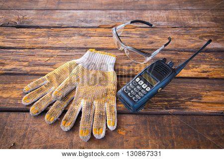 Wireless radio communicationcotton glovessafety glasses on a wooden floor