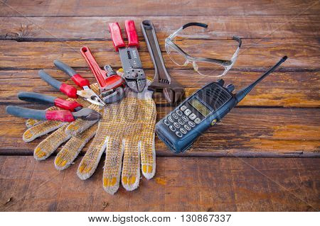 Construction tools on a wooden background with walkie talkie