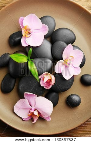 Spa stones and orchid flowers in round plate, top view
