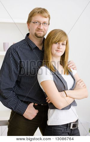 Father and teenage girl posing together at home.