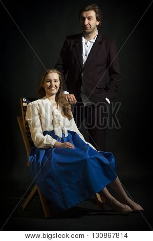 photo of young family couple on black background. girl sitting on a chair. man standing beside her.