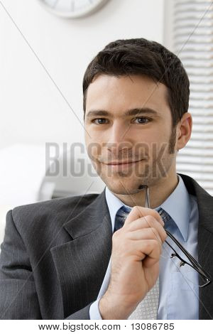 Closeup portrait of young businessman thinking, holding his glasses, smiling and looking at camera.