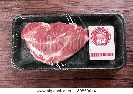 Packed piece of pork meat on wooden background