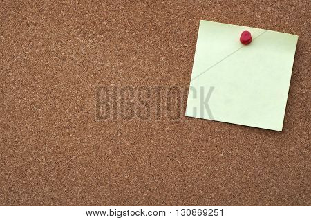 Yellow sticky note on cork board for background.