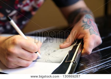 Male hand painting picture in notebook