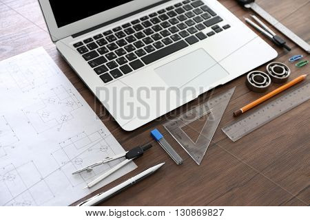 Laptop, engineering drawings and tools on wooden background