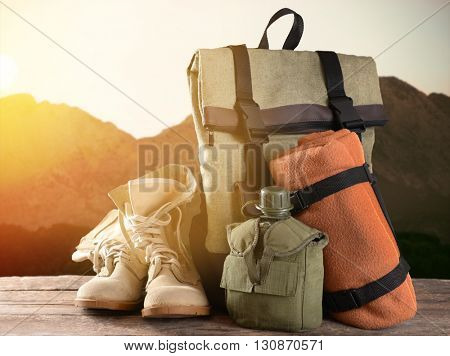 Tourism concept. Backpack, pair of boots and canteen on blurred mountains background