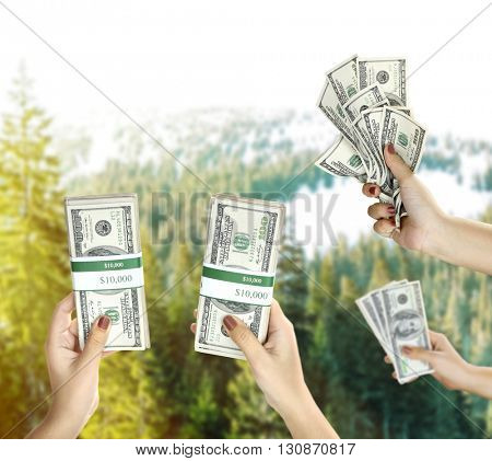 Female hands with dollars on blurred nature background