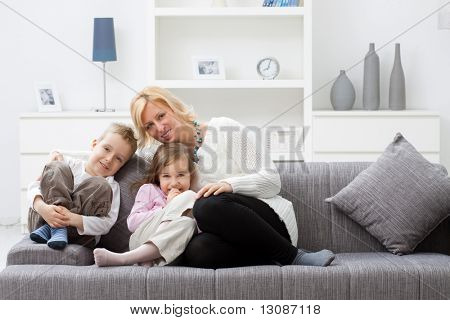 Mother and children sitting together on couch at living room.
