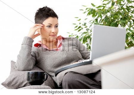 Young woman sitting on couch teleworking on laptop computer at home.
