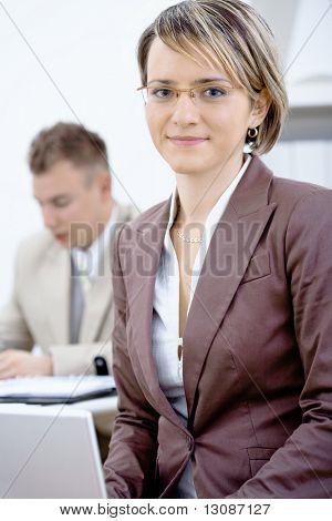Porträt des jungen geschäftsfrau im Amt. Geschäftsmann, arbeiten im Hintergrund.