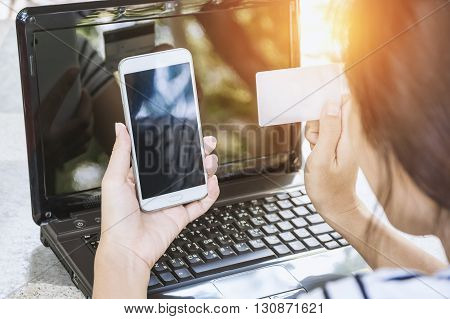 Online payment Woman's hands holding a credit card and using smart phone for online shopping