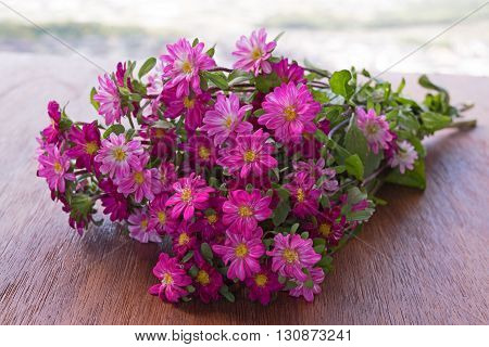 Bouquet of flower asters on a wooden table on a background of the sky