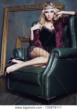 young blond woman wearing crown in fairy luxury interior with empty antique frames total wealth sexual close up