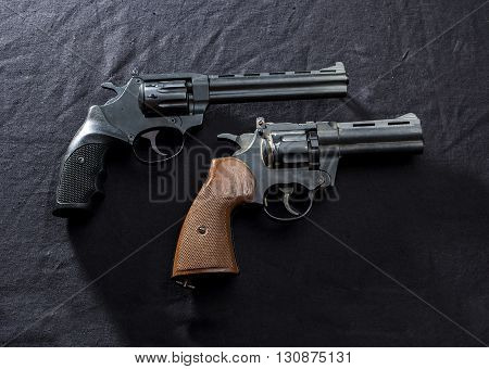 two old revolvers on black background. attack