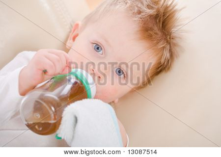 2 years old baby boy drinking from bottle