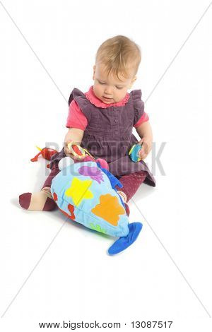 Cute baby girl (1 year old) sitting on floor playing with stuffed animal toy.  Isolated on white, smiling. Toys are offically property released.
