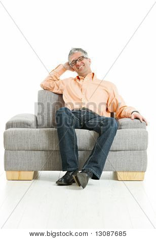 Mid-adult man wearing jeans and orange shirt sitting on couch, talking on mobile phone. Isolated on white.