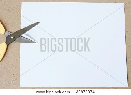 Blank paper and Scissors. Scissors cutting paper on wood table