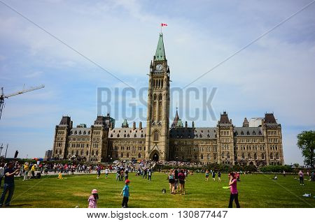 Ottawa Canada - May 21 2016: Parliament Hill in Canadian capital Ottawa a day before Queen Victoria day.Kids and parrent play on the grass.