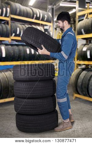 Picture of middle eastern mechanic pile up tires while wearing uniform in the workshop