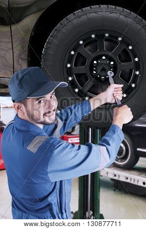 Portrait of Arabic mechanic working in the workshop and replace a car wheel