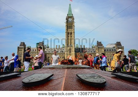 Ottawa Canada - May 21 2016: Parliament Hill in Canadian capital Ottawa a day before Queen Victoria day.People around hero flame at foreground.