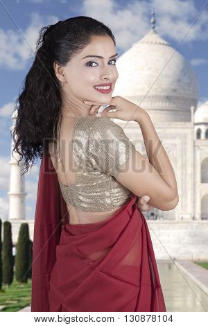 Portrait of cheerful Indian woman smiling at the camera while wearing a red saree clothes with Taj Mahal background