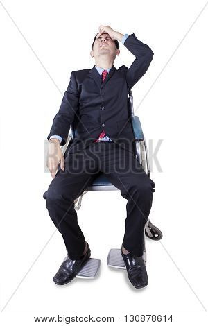 Portrait of handicapped businessman sitting on the wheelchair and looks dizzy isolated on white background
