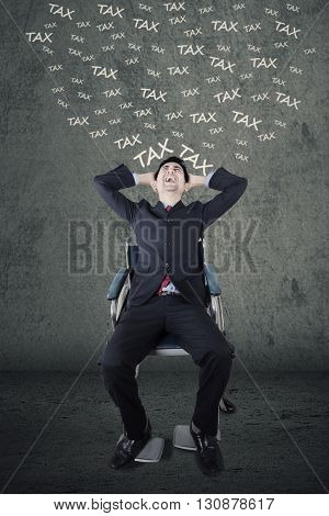 Handicapped businessman sitting on the wheelchair and looks stressful thinking his tax
