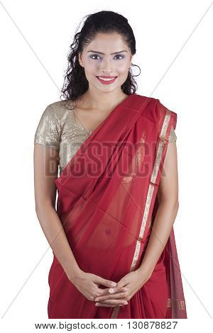 Portrait of a beautiful Indian woman standing in the studio while wearing a red saree isolated on white background