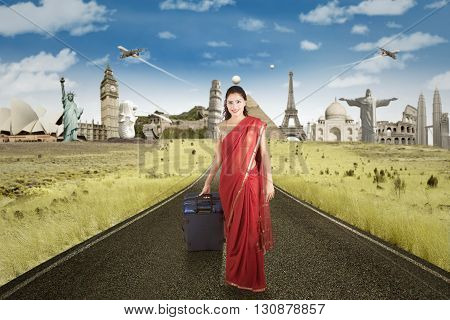 Indian female tourist walking on the road while carrying a suitcase with the world monuments background
