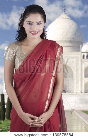 Young Indian woman smiling at the camera while wearing saree clothes with Taj Mahal background