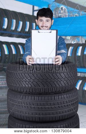 Portrait of male Arabic mechanic showing empty clipboard above a stack of tires in the workshop