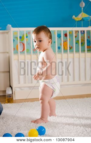 Sweet baby boy ( 1 year old ) in diaper standing at children's room in front of crib.