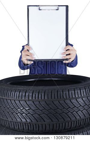 Image of a male mechanic showing empty clipboard above tires isolated on white background