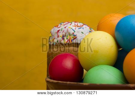 Easter eggs of different colors and cake on a wooden background