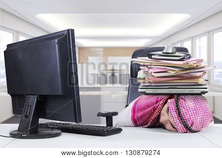Picture of middle eastern worker wearing traditional clothes and sleeping in the office with a pile of paperwork on his head
