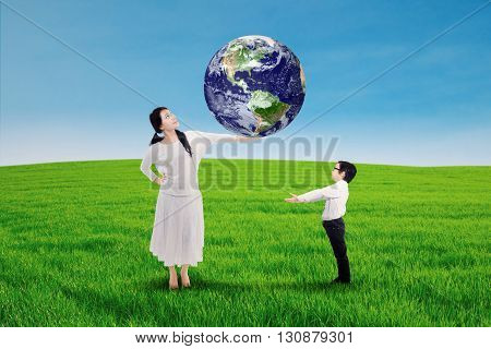 Mother passing the earth to his son. Shot in the meadow