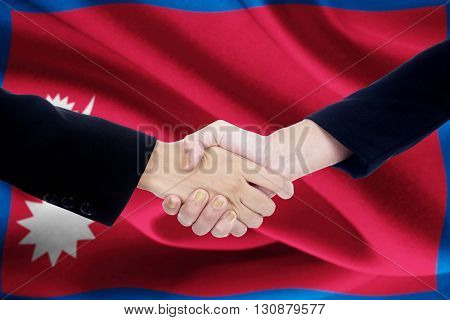 Photo of two worker hands closing a deal by shaking hands with Nepal flag background
