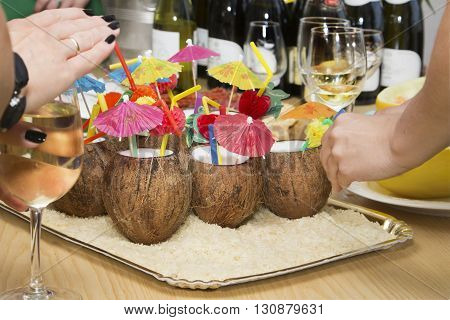 Coconut cocktail with colorful straws and colored paper palm trees wine bottles and woman's hands with wineglasses