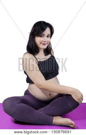 Portrait of a young pregnant woman sitting on the mat while workout isolated on white background