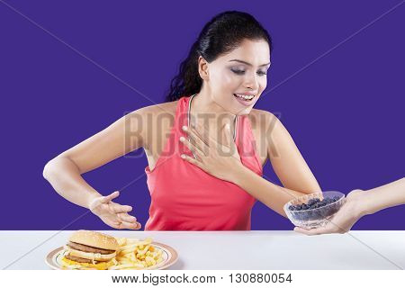 Beautiful indian woman refuse to eat fast food and choose a bowl of blueberry
