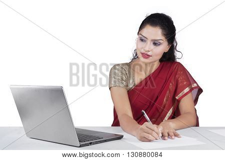 Indian woman wearing sari clothes while working on desk with laptop computer isolated on white background