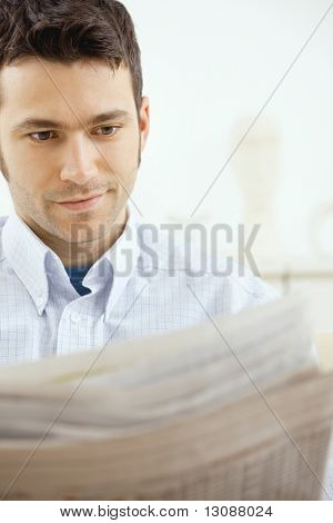 Handsome young man reading newspaper at home.
