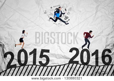 Three young businesspeople racing to get success by jumping and running above numbers 2015 to 2016
