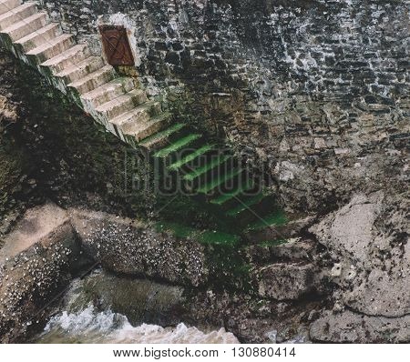 Concrete stairs against a stone wall leading to sea level