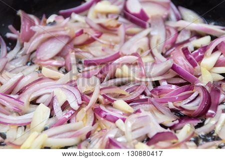 Cooking red onions and garlic in a pan