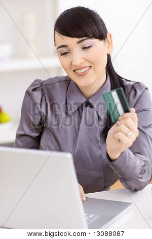 Smiling young women shopping online at home, using laptop computer, holding credit card in hand.