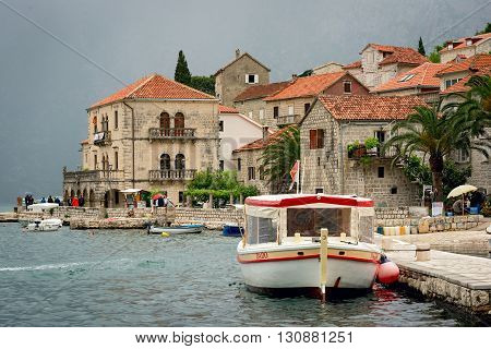 PERAST MONTENEGRO - May 15 2016: Scene of the promenade with old buildings boats locals and tourists. The tiny port in the city centre of Perast makes it even more idyllic and cozy.